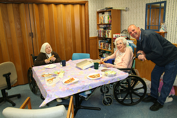 Residents enjoying a pizza lunch with family